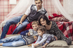 Family mother father children in the bedroom at home drinking te Royalty Free Stock Photo