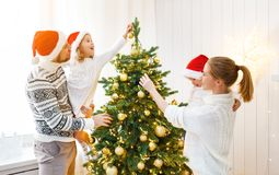 Family mother father and children decorating a Christmas tree at Royalty Free Stock Photos