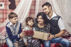 Family mother father and children give each other gifts in your Stock Image