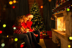 Family - mother, father and kid looking at fireplace in Christmas decorated house interior Stock Photo