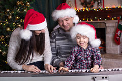 Family - mother, father and kid wearing santa hats playing the piano over christmas background Stock Image