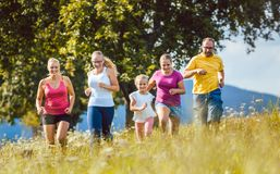 Family, mother, father and kids running for sport. Over a meadow Stock Photo