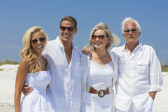 Family Mother Father Son Daughter Couples on Beach. Four people, two seniors, couples or family generations, wearing white clothes together having fun on stock photo