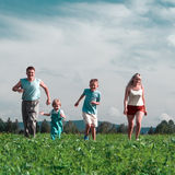 Family mother father and two child run on field stock photos