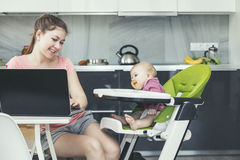 Family the mother feeds the baby in the kitchen happy together a royalty free stock photography