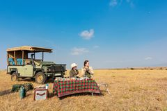 Family safari. Family of mother and her son on African safari vacation enjoying bush breakfast stock image