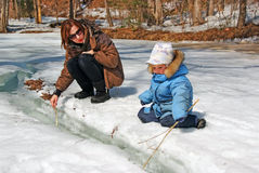 Family of mother with kid playing in the snow spring forest Royalty Free Stock Photo