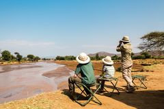 Family safari in Africa. Family of mother and kids on African safari vacation enjoying Ewaso Nyiro River views in Samburu Kenya royalty free stock images