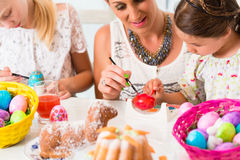 Family with mother and kids coloring Easter eggs Stock Photography