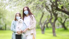 Family of mother and daughter in blooming cherry garden in masks