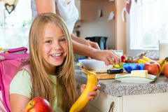 Family - mother making breakfast for school. Family - mother making breakfast for her children in the morning and a snack for school Stock Photos