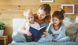 Family mother reading to  children book in bed Royalty Free Stock Photo
