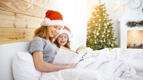 Family mother reads book to child in bed on Christmas morning Stock Photo