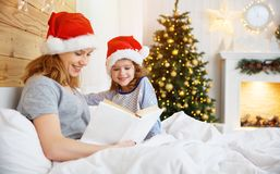 Family mother reads book to child in bed on Christmas morning. Happy family mother reads book to child in bed on Christmas morning Royalty Free Stock Photography