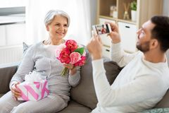Adult son photographing senior mother at home stock image