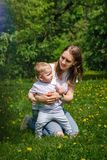 Family. Mother and son. Family. Mom and son are walking in meadow. Girl kneels and hugs little boy stock photography