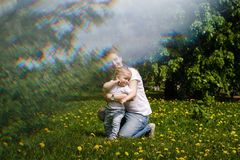 Family. Mother and son outdoors. Family. Mom and son are walking in meadow. Girl kneels, smiles and hugs little boy. Blur effect Stock Photo