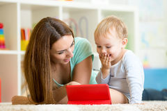 Family - mother and son with tablet on floor at Royalty Free Stock Photos
