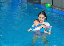 Family of mother teaching baby in swimming pool royalty free stock image