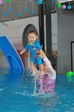Family of mother teaching baby in swimming pool royalty free stock photo