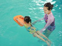 Family of mother teaching kid in swimming pool stock photos