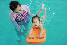 Family of mother teaching kid in swimming pool royalty free stock image