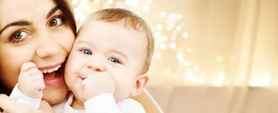 Close up of mother with baby over christmas lights stock photo