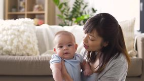 Happy young mother with little baby at home stock footage