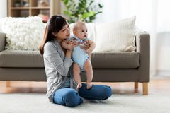 Happy young mother with little baby at home stock image