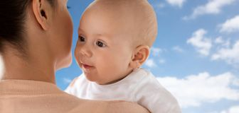 Close up of happy little baby with mother over sky Stock Photo