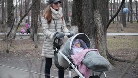 Family, motherhood and people concept - happy mother with baby girl sleeping in stroller walking at spring park.  stock video footage