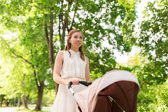 Happy mother with child in stroller at summer park Stock Photo