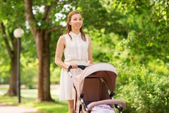 Happy mother with child in stroller at summer park Stock Image