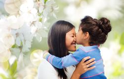 Happy mother and daughter hugging and kissing Stock Photos