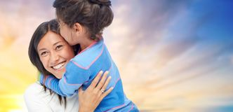 Happy mother and daughter hugging and kissing. Family, motherhood and people concept - happy mother and daughter hugging and kissing over evening sky background stock photos