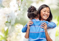 Happy mother and daughter hugging. Family, motherhood and people concept - happy mother and daughter hugging over cherry blossom background royalty free stock photos
