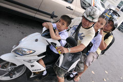 Family on a Motorbike. A family of four makes a school run by motorbike during evening rush hour on September 12, 2011 in Bangkok, Thailand. The use of Royalty Free Stock Image