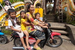 Family on motorcycle. BALI - JANUARY 20. Woman driving her kids to school motorcycle on January 20, 2012 in Bali, Indonesia. Common Balinese cannot afford cars Stock Photo