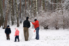 Family Moulding a Snow Man. In the Winter Forest Stock Photos