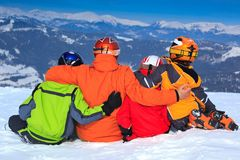 Family on mountain slope. Children and father huddled together in snow on a high mountain slope stock photos