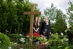 Family mourning at grave on cemetery Royalty Free Stock Image