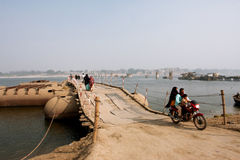 Family moved a motorcycle through the big bridge over the river Ganges Stock Photo