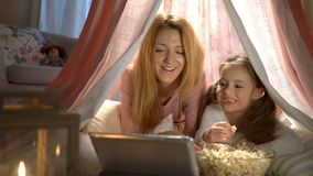 Little girl and her mom enjoying watching cartoons online in the tent in the nursery