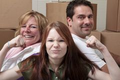 Family moving. Mother, father and daughter leaning on moving boxes Royalty Free Stock Photo
