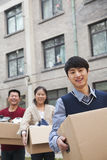 Family moving boxes into a dormitory at college, smiling and looking at camera Royalty Free Stock Photo