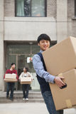 Family moving boxes out of a dormitory at college, son smiling Stock Photo