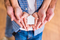 Family moving home. Hands of a happy young family holding little house, moving to a new home stock photography