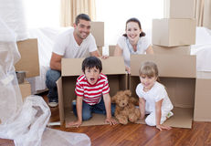 Family moving house with boxes around. Happy family moving house with boxes around Royalty Free Stock Image
