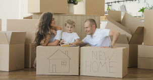 Family moving house. Family plays in their new apartment. family relaxing and laughing after unpacking cartons from stock footage