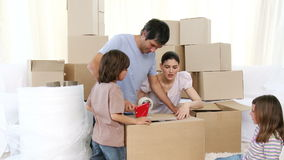 Family moving house unpacking boxes. Footage in high definition of young parents and children moving house unpacking boxes stock footage